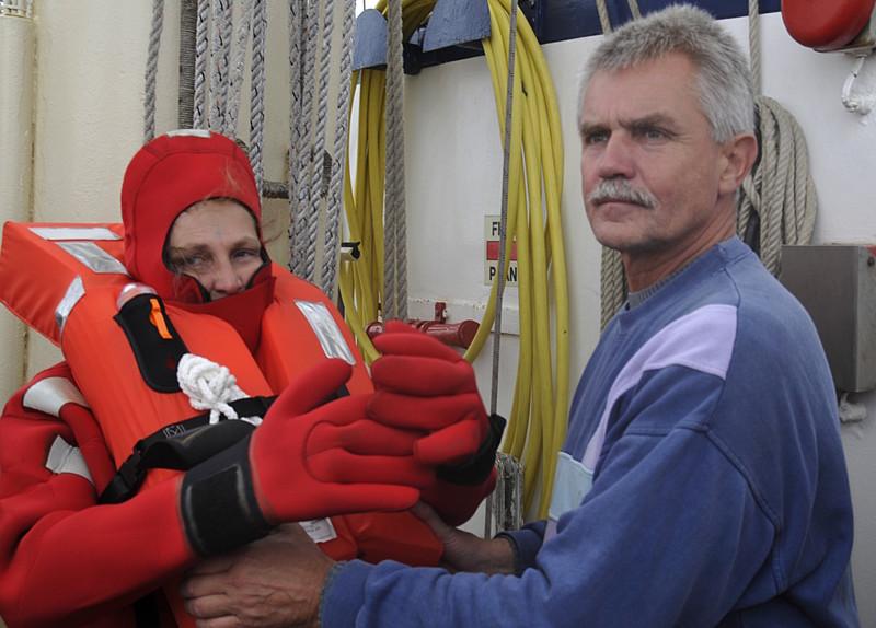 SSS Greif 10 Brigitte Denck im Rettungsanzug mit Uwe Kiessling Hand fuer Koje Toern Ostsee 2014-09-26 QF Copyright Foto Knut Hildebrandt