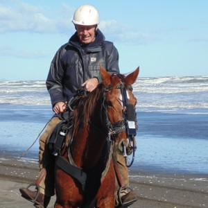 Fig.5b. Hanson in the saddle with his 11-year-old half-bred mare wearing his copy of a Bedouin noseband attached to the head collar supporting the exercise video-endoscope in the mare's right nasal cavity. The audio-recorder lies above the white label. 2015 © Robert Cook, photo: Fridtjof Hanson
